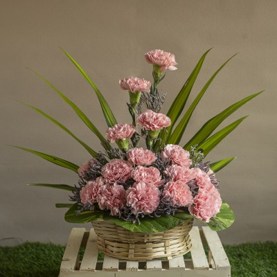 Arrangement of Pink Carnations and Leaves in a basket