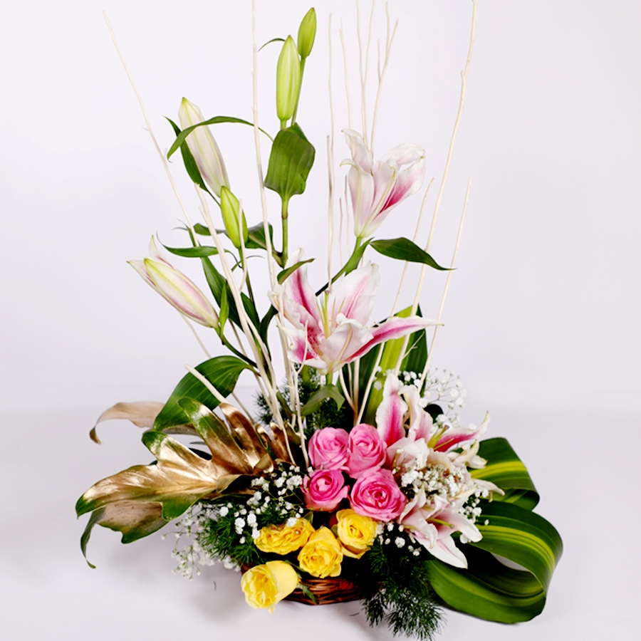 Basket of lillies and roses with dry sticks