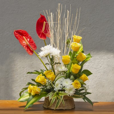 Arrangement of Yellow Roses ,White Chrysanthemums ,Anthroniums and Dry sticks in a basket