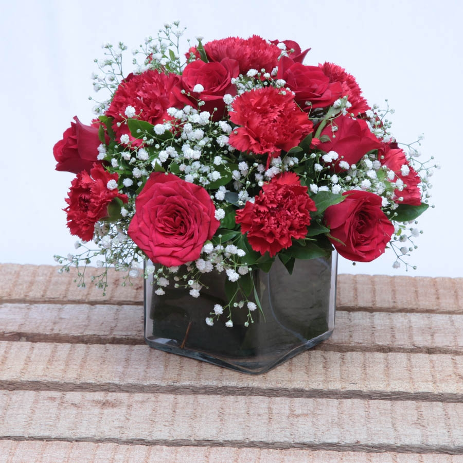 square glass vase of red roses